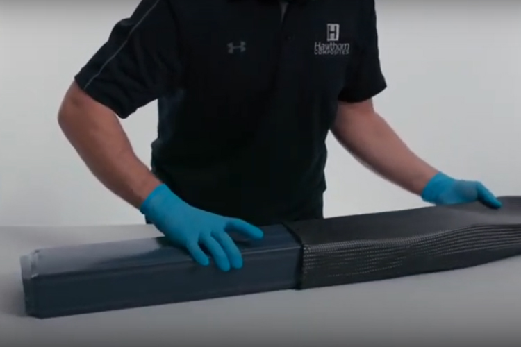 To start, they pull braided biaxial dry carbon fiber sleevings over each of the three smart tools to create the sheer webs and part of the structure of the control surface.