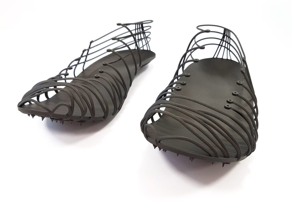 Front view Pleko track spikes with outsole, midsole, pins and ribbing 3D printed as single unit in Carbon fiber filled composite material Windform® SP. Courtesy CRP Technology/Miro Buroni